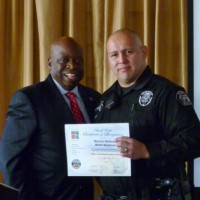 Mayor Al Murray presents a City of Tustin certificate of recognition to Officer Rene Barraza.